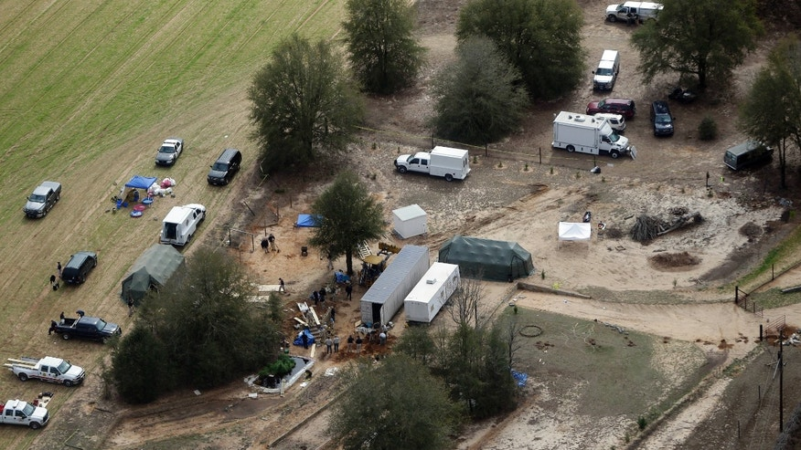 Authorities continue their investigation at the site in Midland City, Ala., on Friday, Feb. 8, 2013 where a five year old boy was held hostage in an underground bunker before being rescued Monday. Authorities shot and killed Jimmy Dykes after a week long standoff. The boy who was freed from an underground bunker is acting like a typical 5-year-old by all accounts, playing with toys and running around, but psychology experts and a woman who suffered through a similar ordeal warn there could be long-term emotional scars. (AP Photo/Dave Martin)