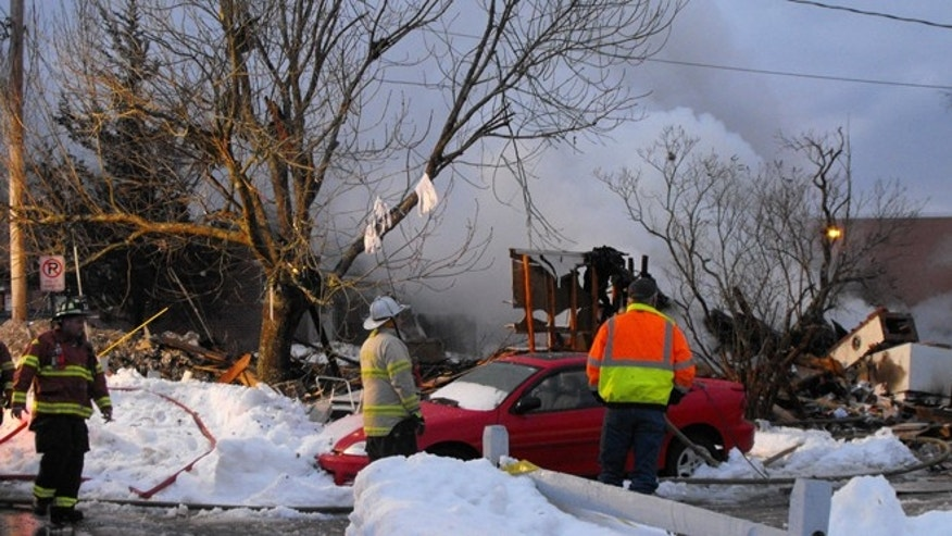 Feb. 12, 2013: Firefighters survey the remains of a fire after an explosion at a duplex apartment in Bath, Maine.