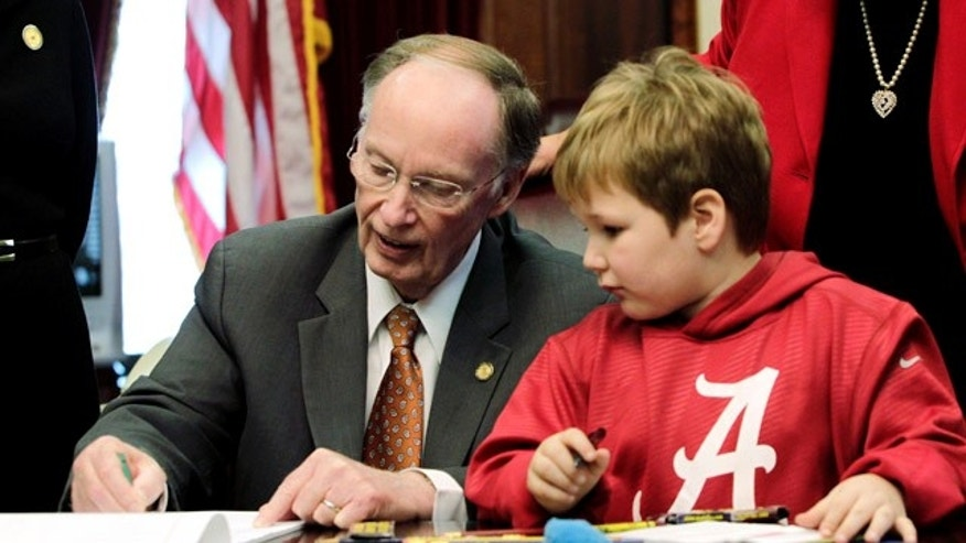 Feb. 13, 2013: Gov. Robert Bentley, left, draws with 6-year-old Ethan Gilman during a visit to the Governor's Office in Montgomery, Ala.