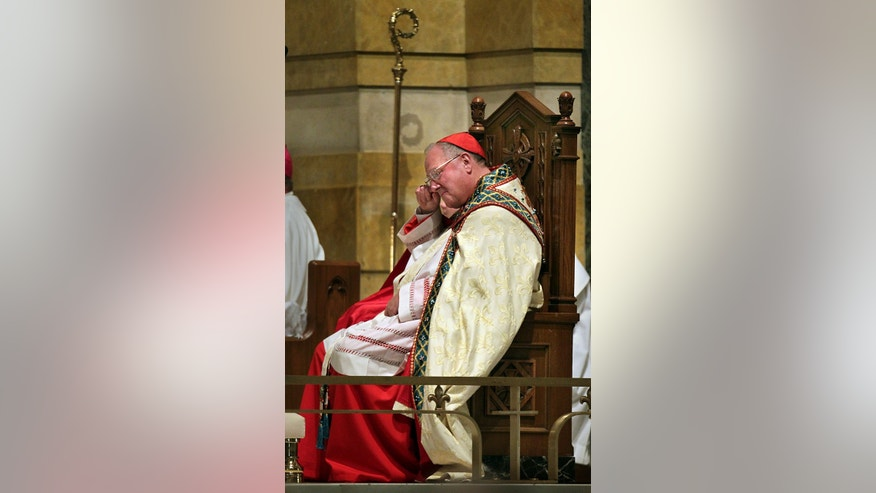 In this photo taken on Saturday, Jan. 26, 2013, Cardinal Timothy Dolan, archbishop of New York, listens to Bob Costas as he eulogizes Stan Musial during his funeral at the Cathedral Basilica in St. Louis. Prevailing modern wisdom has been that an American — or a citizen of any superpower — could not be elected pope. Many Vatican watchers still think that's true, but others say that Dolan, a Ballwin native, may represent the first real prospect of an American pontificate. (AP Photo/St. Louis Post-Dispatch, Robert Cohen)  EDWARDSVILLE INTELLIGENCER OUT; THE ALTON TELEGRAPH OUT
