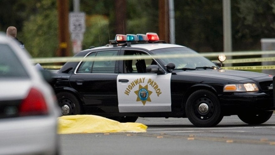 Feb. 19, 2013: A body lays in the intersection of Wanda Road and Katella Avenue in Orange County, Calif.,  as local police agencies investigate the scene.