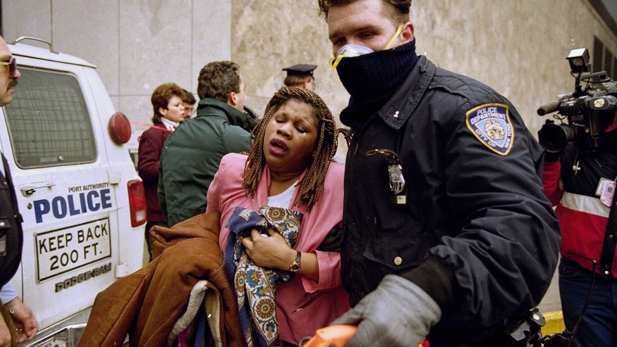 FILE -  In this file photo of Feb. 26, 1993, a New York City police officer leads a woman to safety following a  bomb blast at the World Trade Center. Twenty years ago next week, a group of terrorists blew up explosives in an underground parking garage under one of the towers, killing six people and ushering in an era of terrorism on American soil. (AP Photo/Alex Brandon, File)