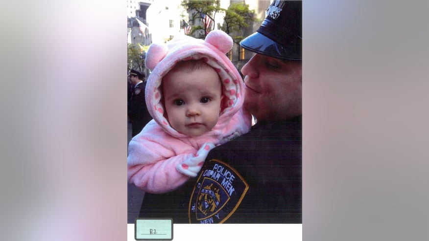 This undated photo submitted into evidence by Assistant Federal Defender Julia L. Gatto shows Gilberto Valle with his daughter. Valle is accused of conspiracy to kidnap a woman and unauthorized use of a law enforcement database that prosecutors say he used to help build a list of potential targets. Gatto tried to soften the image of her client by showing jurors pictures of a uniformed Valle and the coupleís 1-year-old daughter, a moment that caused the wife on the witness stand and eventually the officer at the defense table 30 feet away to cry out amid sobs. (AP Photo/Assistant Federal Defender Julia L. Gatto)