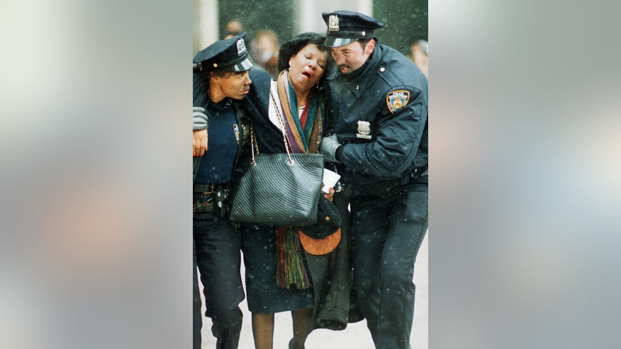 FILE - In this file photo of Feb. 26, 1993, two New York City police officers help an injured women away from the scene of the World Trade Center explosion. Twenty years ago, a group of terrorists blew up explosives in an underground parking garage under one of the towers, killing six people and ushering in an era of terrorism on American soil.  (AP Photo/Joe Tabacca, File)