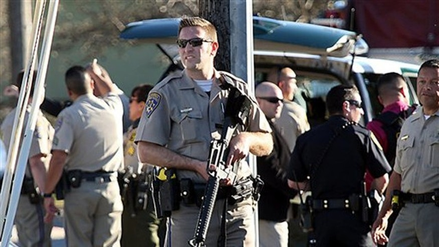 Feb. 26, 2013: A California Highway Patrol officer carries his rifle near the shooting scene in Santa Cruz, Calif.