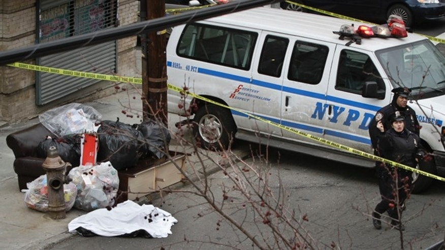 Feb. 26, 2013: Police guard a sheet-covered plastic bag, left, on Eagle Avenue in the Bronx borough of New York.