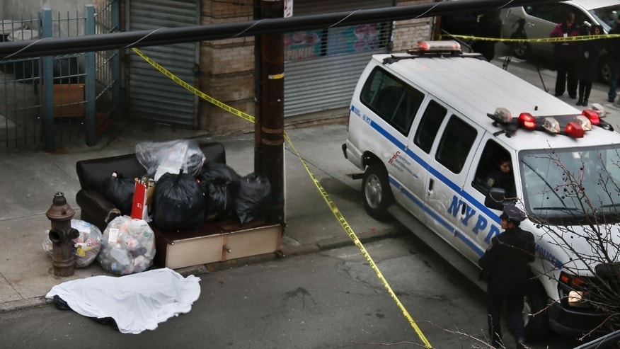 Police guard a sheet-covered plastic bag near the intersection of Eagle Avenue and 158th street in the Bronx, on Tuesday, Feb. 26, 2013 in New York.  A man out walking his dog earlier made a gruesome discovery of the dismembered remains of a woman in plastic garbage bags, police said. (AP Photo/Bebeto Matthews)