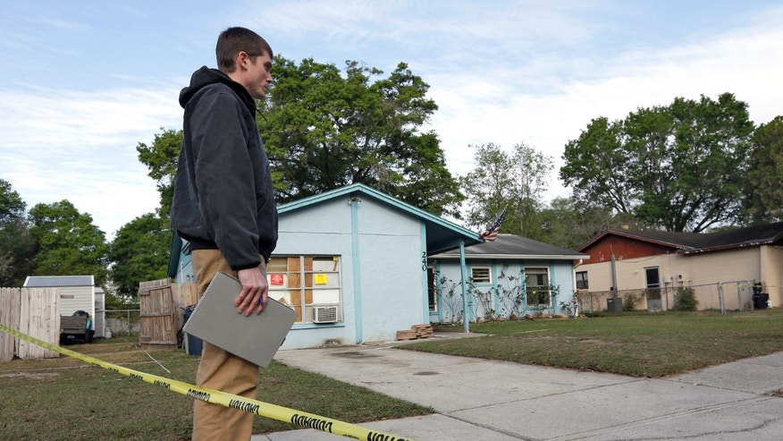 March 1, 2013: An engineer stands in front of a home where sinkhole opened up in Seffner, Fla.