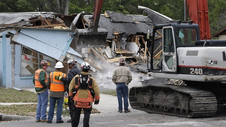 March 3, 2013: Demolition experts watch as the home of Jeff Bush, 37,  is destroyed, after a sinkhole opened up underneath it late Thursday evening swallowing Bush, 37, in Seffner, Fla. The 20-foot-wide opening of the sinkhole was almost covered by the house, and rescuers said there were no signs of life since the hole opened Thursday night.