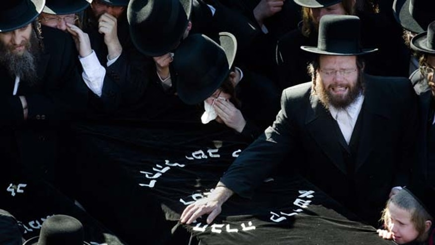 March 3, 2013: Members of the Satmar Orthodox Jewish community grieve over the coffins at the funeral for two expectant parents who were killed in a car accident.