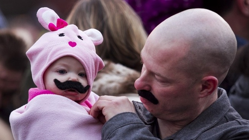 March 7, 2013: Gwyneth, 6 months, and Randy Roest wear false mustaches as a crowd attempts to break the Guinness World Record for the most people wearing false mustaches to kick off Gilda's LaughFest 2013 in Grand Rapids, Mich. (AP)