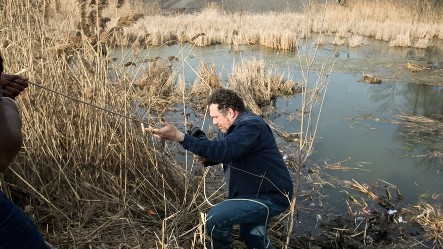 March 10, 2013: Beduareo Marquez climbs up the pond embankment where he retrieved a shoe from the crash site that six teens died on Park Ave. in Warren, Ohio.