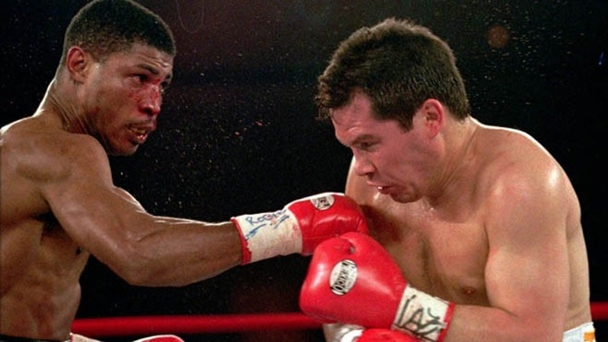 March, 29,1997: In this file photo, Tony Martin, left, of Philadelphia, punches Mexico's Julio Cesar Chavez in the second round of their Welterweight Special Attraction fight, in Las Vegas. Police say that Martin, a former welterweight, was fatally shot Friday, March 8, 2013, in an altercation with a visitor at one of his rental properties in Philadelphia.  He was 52.