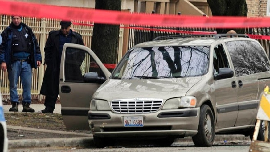 March 11, 2013: In this file photo, Chicago Police investigate at the scene of a shooting where 6-month-old Jonylah Watkins, was shot five times whie her father was changing her diaper in a parked minivan in Chicago's Woodlawn neighborhood. The van can be seen with the window shattered from the shooting.