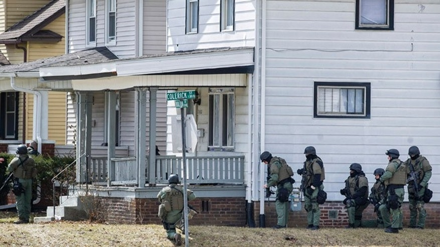 March 20, 2013: Armed officers surround a house in Fort Wayne, Ind., where police say a man suspected of killing a bus passenger earlier in the day is holding a 3-year-old child hostage.