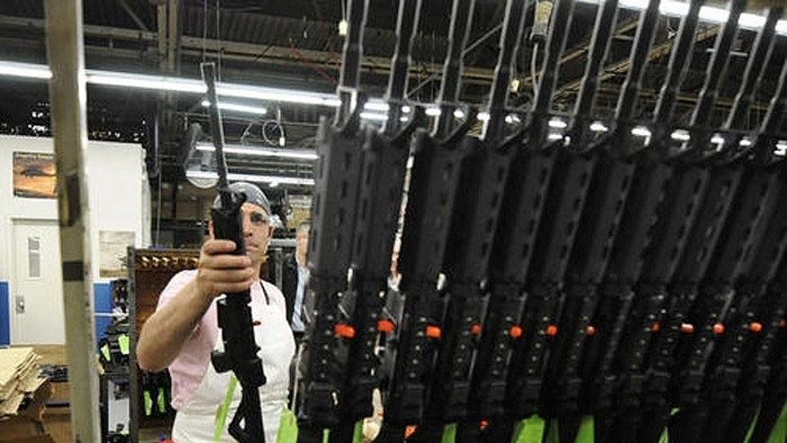 Sergio Pereira adds a completed Colt rifle to a rack of newly assembled guns at the company headquarters in West Hartford. (Michael McAndrews/The Hartford Courant)