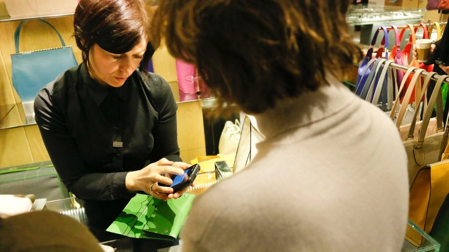 Feb. 15, 2013: A sales staff member at Barney's New York uses an iPod Touch to help a customer make a purchase, in New York.