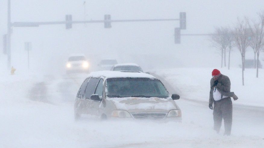 A man waits for help after becoming stuck in snow along West 6th Street in Lawrence, Kan., Sunday, March 24, 2013. Few signs of spring are being found in parts of the Midwest as a snowstorm brings heavy snow and high winds. (AP Photo/Orlin Wagner)
