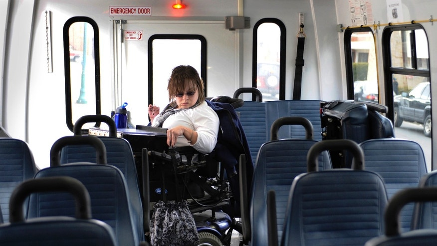 In this photo taken Friday, March 1, 2013, Jennifer Lortie maneuvers herself into a bus during her two-hour commute home after work in Willimantic, Conn. Of the 29 million workingage Americans with a disability Lortie, who has limited arm and leg use due to cerebral palsy, is one of the 5.1 million disabled Americans who are actually employed. The National Council on Disability's Jeff Rosen says long-standing prejudicial attitudes need to be addressed to boost jobs. (AP Photo/Jessica Hill)