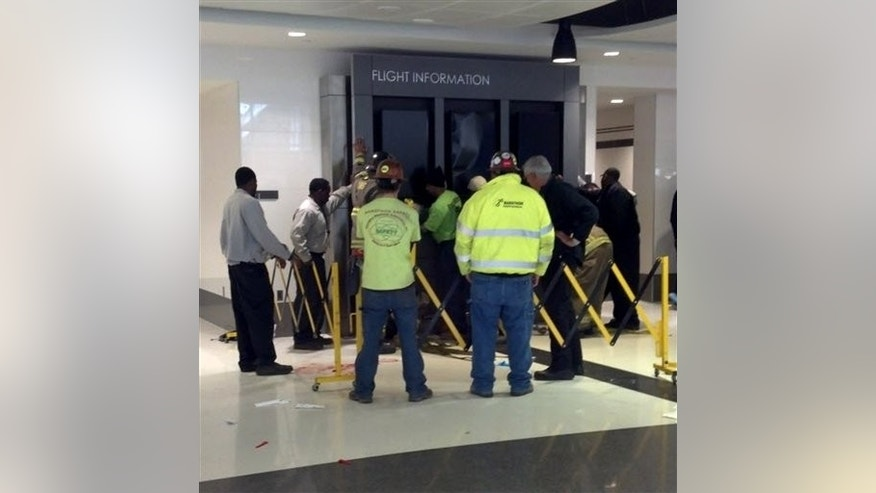 March 22: People hold up a message board sign that fell on a family killing a child and injuring the mother and two other children in the terminal at the Birmingham-Shuttlesworth International Airport in Birmingham, Ala.