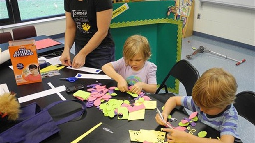In this Thursday, Aug. 4, 2011 photo, Parent volunteer Trinity Laurino, left, works on bulletin board decorations at Toomer Elementary School in Atlanta with her daughter, Olivia Laurino, center, and friend, Jake Jonsson in Atlanta. Atlanta Public Schools returns to classes Monday, Aug. 8, 2011.