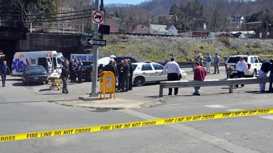 April 3: Law enforcement officers and emergency service personnel converge on the scene of the shooting in downtown Williamson, W.Va., where Sheriff Eugene Crum was shot and killed at point blank range.