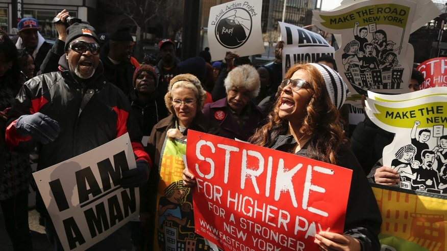 April 4, 2013: Demonstrators holds a sign and chant slogans outside of a Wendy's fast food restaurant in New York.  New York City fast food workers plan a second job action day to press for higher wages.