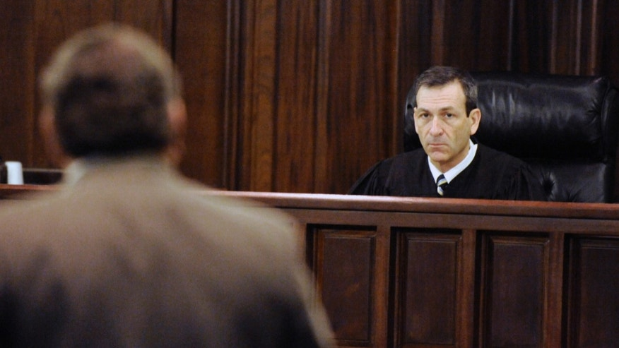 Superior Court Judge Stephen Kelly, right, listens to a motion during the bond hearing for De'Marquise Elkins,  Friday April 5, 2013 in Brunswick, Ga. Authorities charged Elkins with malice murder for the March 21 slaying of 13-month-old Antonio Santiago.  Police say the child was shot as Elkins and a younger teenager tried to rob the boy's mother.  Kelly denied Elkins' request for bond Friday, saying he's concerned Elkins might flee. (AP Photo/Stephen Morton)