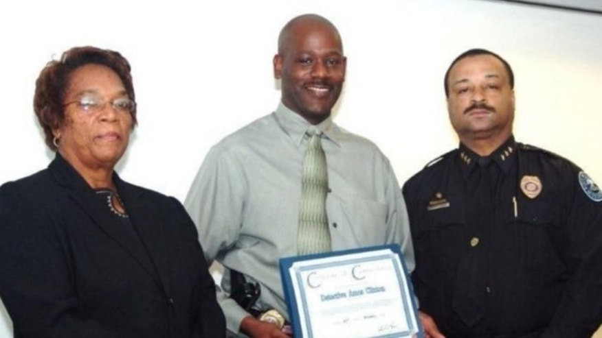 UNDATED: In this 2008 image provided by the Jackson, Miss. Police, Detective Eric Smith, center, flanked by Chief Rebecca Coleman, left, and Assistant Chief Lee Vance accepts the Certificate of Commendation on behalf of Detective Amos Clinton in Jackson, Miss.