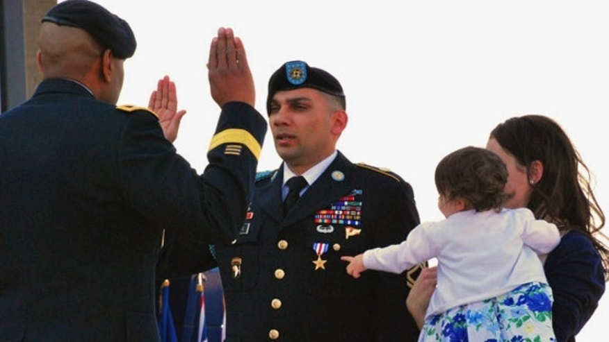 April 5, 2013: Sgt. 1st Class Matthew Loheide re-enlists in the Army at Fort Campbell, Ky., while his daughter, Annabella, held by Marianne Loheide, points to his Silver Star. Loheide received the Silver Star for his actions to evacuate wounded soldiers while in Afghanistan in 2010.