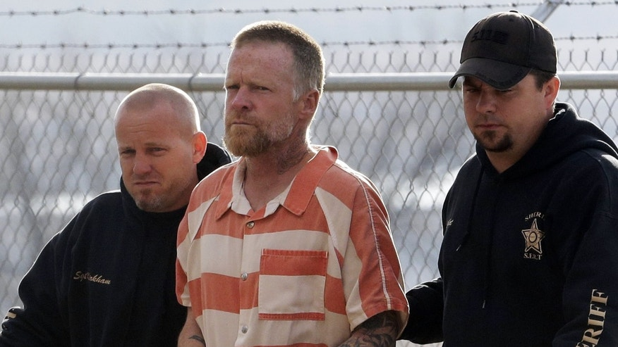 """Sanpete Sheriff's Officers escort Troy James Knapp, 45, to the Sanpete County Jail Tuesday, April 2, 2013, in Manti, Utah. Authorities captured Knapp, an elusive survivalist who is suspected of burglarizing Utah cabins and leaving some covered with threats and bullet holes, ending a saga that began six years ago and drew in police and residents around the state. Knapp, dubbed the """"Mountain Man"""" by cabin owners, was taken into custody in the snowy mountains outside of Ferron in central Utah after firing several shots at officers in a helicopter, authorities said. (AP Photo/Rick Bowmer)"""