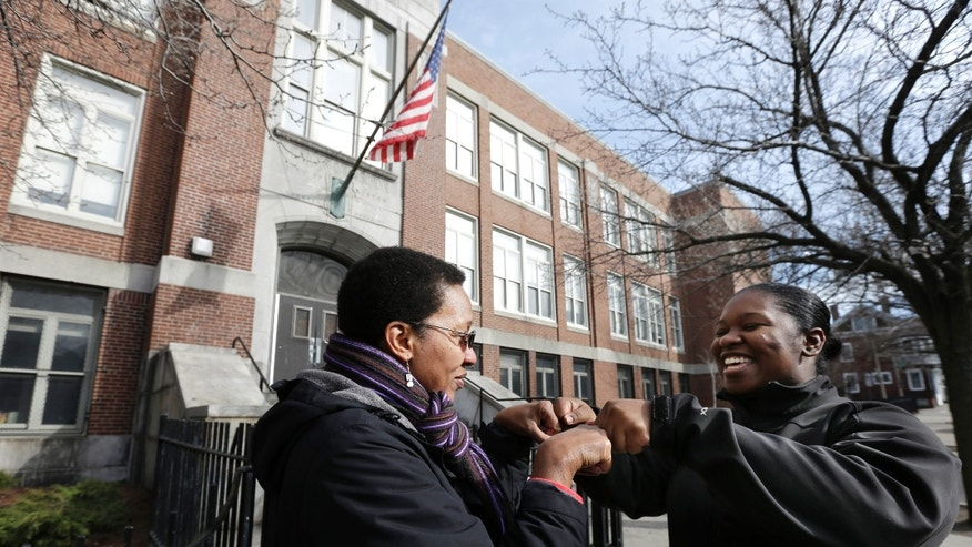 In this March 28, 2013 photo, Ginnette Powell, left, and her friend Jonnelle Seigler, both of Boston, fist bump during a chance meeting in front of the UP Academy Charter School in Boston's South Boston neighborhood. Powell was bussed to the predominantly white neighborhood almost 40 years ago to attend school at what was Patrick Gavin Middle School. She said will never forget riding the school bus as protesters hurled bricks at it. (AP Photo/Steven Senne)