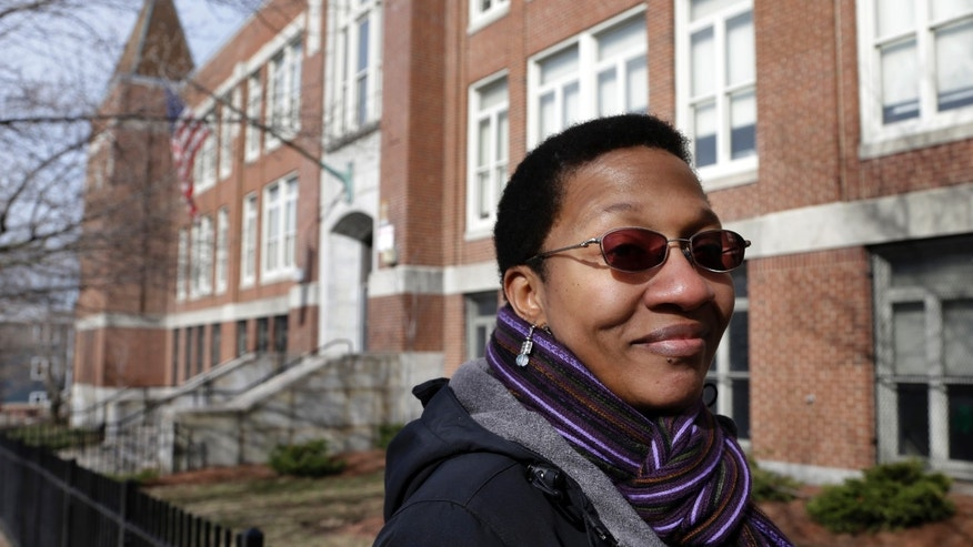 In this March 28, 2013 photo, Ginnette Powell, of Boston, stands in front of the UP Academy Charter School in Boston's South Boston neighborhood. Powell was bussed to the predominantly white neighborhood almost 40 years ago to attend school at what was Patrick Gavin Middle School. She said will never forget riding the school bus as protesters hurled bricks at it. (AP Photo/Steven Senne)