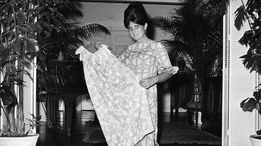 In this March 16, 1965 file photo, Palm Beach the fashion designer Lilly Pulitzer, wears her own design and creation of the Lilly shift, in Palm Beach, Fla. Pulitzer, known for her tropical print dresses, dies in Florida at 81.