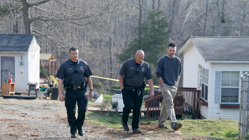 Two Lincoln County Sheriff's deputies walk with a man Monday, April 8, 2013, from the scene at the end of Cedarbrook Court near Stanley, N.C., where two children were killed Sunday when a wall of dirt fell on them while they were playing in a hole at a home construction site. (AP Photo/Bob Leverone)