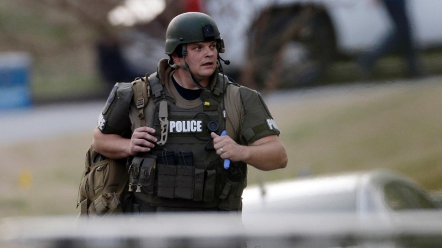 A police officer runs after an explosion and gunshots were heard near the scene where a man was holding four firefighters hostage Wednesday, April 10, 2013 in Suwanee, Ga. A police spokesman said the suspect was dead and none of the hostages suffered serious injuries.  (AP Photo/John Bazemore)