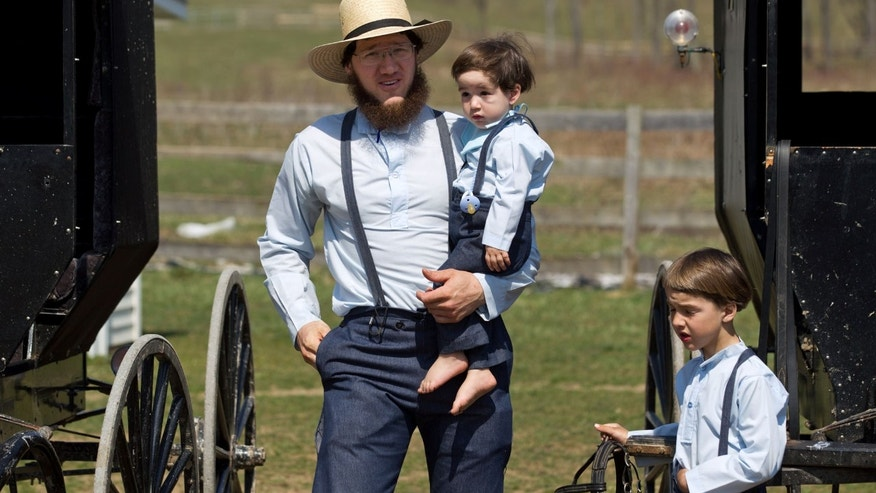 HOLD FOR STORY Freeman Burkholder carries his son to the school house for the end of the school year celebration in Bergholz, Ohio on Tuesday, April 9, 2013.  Burkholder is one of the Amish members convicted in a beard and hair cutting scandal against other Amish people.  (AP Photo/Scott R. Galvin)