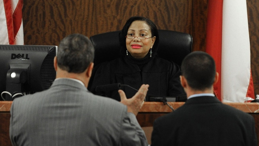 Jules Laird, left, defense attorney for Dylan Quick, and prosecutor Joshua Phanco, right, talk with Judge Maria Jackson Thursday, April 11, 2013, in Houston. Quick, alleged to have wounded more than a dozen people at a Houston area Lone Star College campus, had his arraignment postponed so he can be mentally evaluated. (AP Photo/Pat Sullivan)
