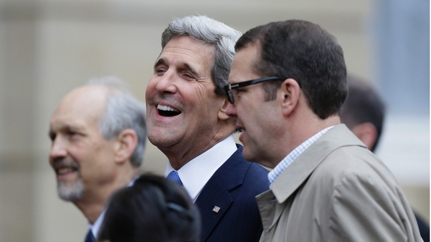 U.S. Secretary of State John Kerry, laughs as he talks to his staff during a break at a G8 Foreign Ministers meeting in London, Thursday, April, 11, 2013. The ministers are meeting in London as Britain currently holds the G8 Presidency, with the heads of government G8 meeting set for June in Northern Ireland.(AP Photo/Alastair Grant)