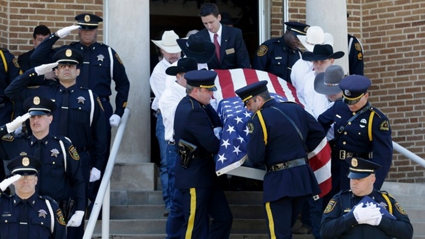 April 5, 2013: Pallbearers carry the remains of Kaufman County District Attorney Mike McLelland and his wife, Cynthia, out of the First Baptist Church of Wortham after their funeral services in Wortham, Texas.