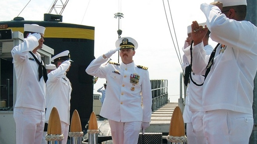 Aug. 3, 2013: In this photo provided by the U.S. Navy, Cmdr. Michael P. Ward II, center, is saluted during the change-of-command ceremony for the nuclear submarine USS Pittsburgh at the Naval Submarine Base New London, in Groton, Conn.