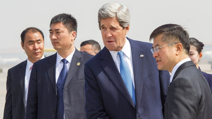 U.S. Secretary of State John Kerry, center, is greeted by U.S. Ambassador to Chjina Gary Locke upon arrival at Beijing Capitol International Airport Saturday, April 13, 2013 in Beijing. (AP Photo/Paul J. Richards, Pool)