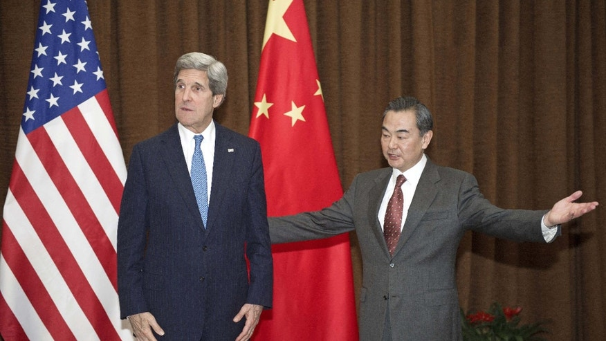 U.S. Secretary of State John Kerry, left, is escorted by Chinese Foreign Minister Wang Yi prior to their meeting at the Chinese Foreign Ministry Saturday, April 13, 2013 in Beijing. The question of how Washington can persuade Beijing to exert real pressure on North Korean leader Kim Jong Un's unpredictable regime is front and center as Kerry meets Saturday with Chinese leaders in Beijing. (AP Photo/Paul J. Richards, Pool)
