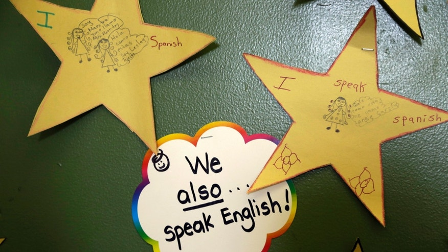 """In this April 3, 2013 photo, a sticker reading, """"We also speak English,"""" hangs with writings in Spanish on the wall of a classroom at the Coral Way K-8 Center, the nation's largest bilingual school, in Miami. Students who speak a language other than English at home are one of the fastest-growing populations. (AP Photo/Lynne Sladky)"""