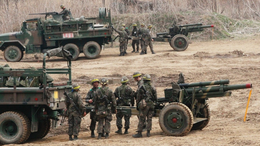 South Korean army soldiers conduct military exercise in Paju, South Korea, near the border village of Panmunjom, Tuesday, April 16, 2013.  North Koreans danced in plazas and snacked on peanuts as part of holiday festivities while the Supreme Command led by North Korean leader Kim Jong Un offered more of the fiery language that has made the international community wary of an imminent missile launch or other provocation.(AP Photo/Ahn Young-joon)