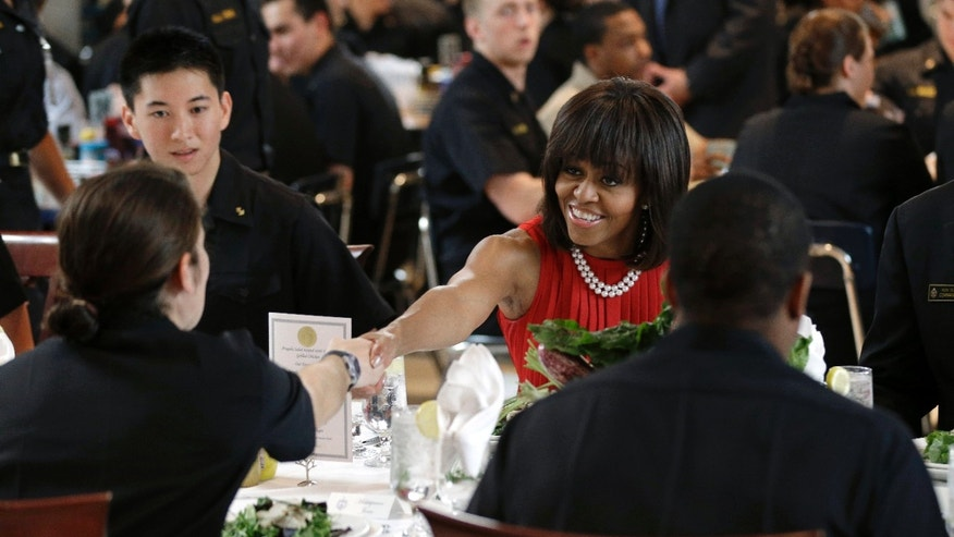 First lady Michelle Obama shakes hands with Midshipman First Class Jenny Jones as they sit down for lunch at the U.S. Naval Academy in Annapolis, Md., Wednesday, April 17, 2013. Obama visited with midshipmen who will be affected by Maryland's new Veterans Full Employment Act of 2013. The bill, passed by the Maryland General Assembly, creates an expedited licensing procedure for veterans and military spouses who hold professional licenses in other states. It also requires Maryland's public colleges and universities to develop policies to award academic credit for relevant military training and education. (AP Photo/Patrick Semansky)