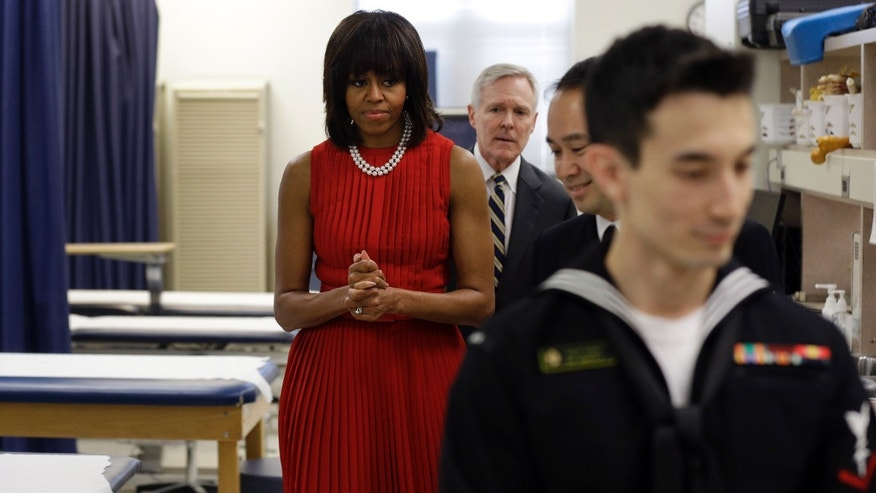 First lady Michelle Obama and Navy Secretary Ray Mabus, back, tour an orthopedic room with midshipmen at the U.S. Naval Academy in Annapolis, Md., Wednesday, April 17, 2013. Obama visited with midshipmen who will be affected by Maryland's new Veterans Full Employment Act of 2013. The bill, passed by the Maryland General Assembly, creates an expedited licensing procedure for veterans and military spouses who hold professional licenses in other states. It also requires Maryland's public colleges and universities to develop policies to award academic credit for relevant military training and education. (AP Photo/Patrick Semansky)