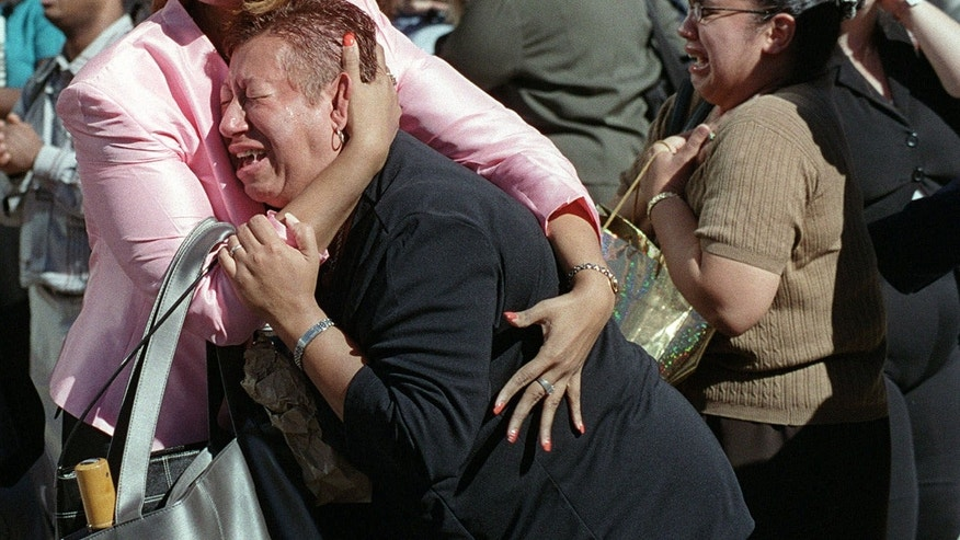 FILE - In this Tuesday, Sept. 11, 2001 file photo, two women embrace each other as they watch the World Trade Center burn following a terrorist attack on the twin skyscrapers in New York. (AP Photo/Ernesto Mora) MANDATORY CREDIT