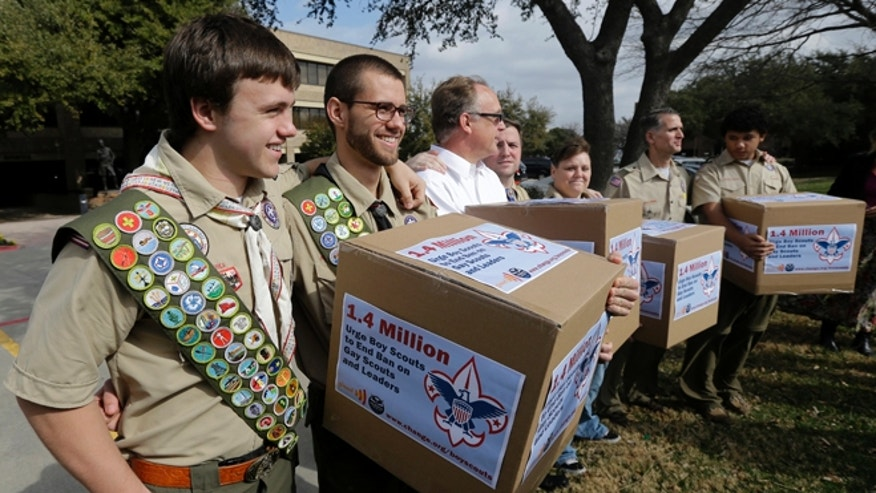 Feb. 4, 2013: In this file photo, James Oliver, left, hugs his brother and fellow Eagle Scout, Will Oliver, who is gay, as Will and other supporters carry four boxes filled with a petition to end the ban on gay scouts and leaders in front of the Boy Scouts of America headquarters in Dallas, Texas.