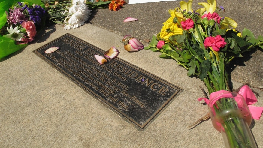 In this April 5, 2013 photo, flowers are seen at the plaque dedicated to life and achievements of movie critic Roger Ebert in front of his boyhood home in Urbana, Ill., the day after the Pulitzer Prize-winning critic died at age 70 after a long battle with cancer. Through his television shows, movies reviews and essays, Ebert belonged to the world beyond Urbana. One part of Ebert's life that got little attention as the nation mourned his sudden death was how much he meant to this university town where he grew up.  (AP Photo/David Mercer, File)